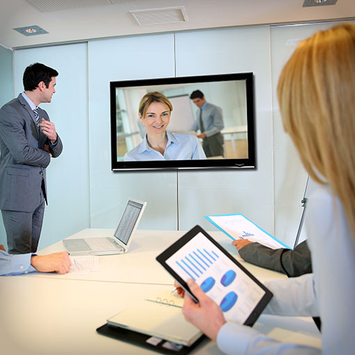 Business Peaople havinga a meeting with one colleague joining remotely via big screen